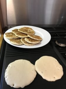 Two pancakes cooking on a griddle with a plate of finished pancakes behind them.